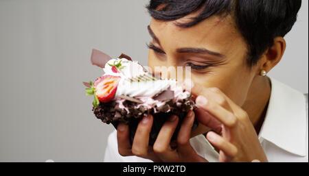 Black woman making a mess eating a huge fancy dessert - Stock Photo