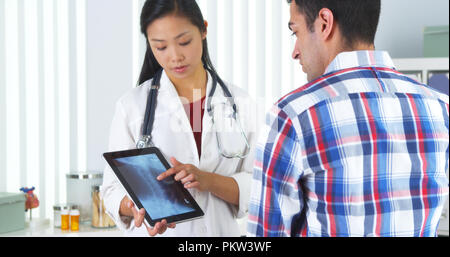 Chinese doctor going over xray with patient - Stock Photo