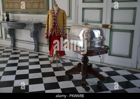 Black and white checker tile floor in the castle with a dummy in full dining regalia and a silver dish on a tray - Stock Photo