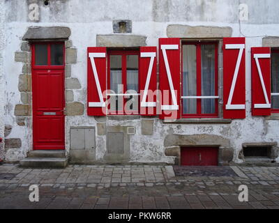 Bright red shutters on a typical stone beach house on the west coast of France by a cobblestone street - Stock Photo