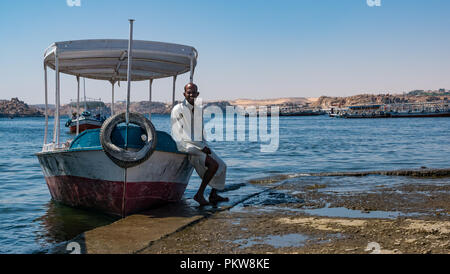 Local Egyptian man in traditional white robe with boat on Lake Nasser waiting to transport tourists to Philae Temple, Aswan, Egypt, Africa - Stock Photo