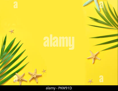 Tropical background. Palm trees branches with starfish on yellow background. Travel. Copy space - Stock Photo