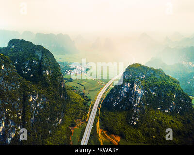 Aerial photo of karst mountains and highway in China on a foggy day - Stock Photo