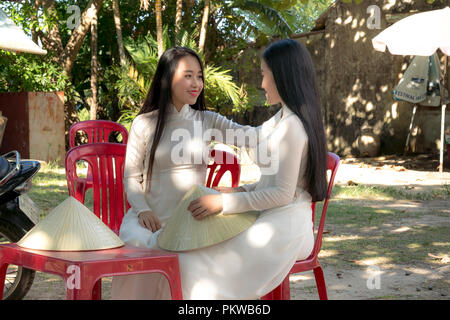 Two Vietnamese girls are gentle in culture traditional white long dress at Hue city, Vietnam - Stock Photo