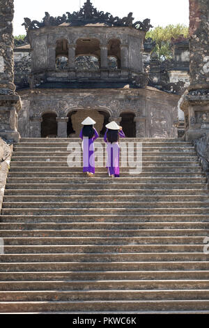 Two Vietnamese girls are gentle in culture traditional purple long dress at the Tomb of Khai Dinh King at Hue city, Vietnam - Stock Photo
