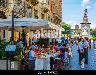 Pavement cafe in Dante street and Sforza Castle. - Stock Photo