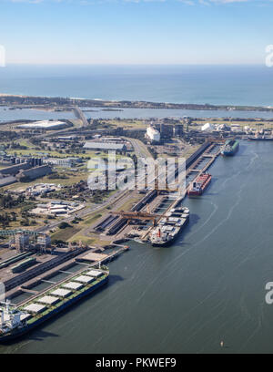 Four ships being loaded with coal for export at Kooragang Island Newcastle Australia. Newcastle is one of the biggest coal export port in the world se - Stock Photo