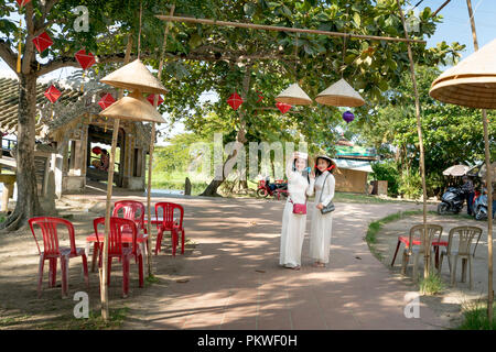 Two Vietnamese girls are gentle in culture traditional white long dress is taking self-portrait for each other at Thanh Thuy Chanh Village in Hue city - Stock Photo