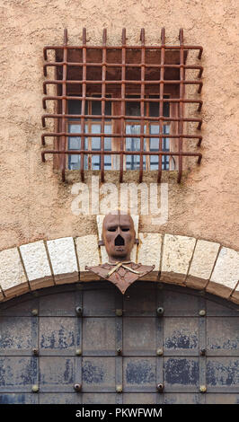Iron Mask above an old gate in Le Suquet on the Tour du Masque, a tower that is haunted by the ghost of the man in the Iron Mask near the castle of Ca - Stock Photo