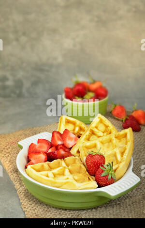 Waffles with fresh ripe red strawberries served on a plate - Stock Photo