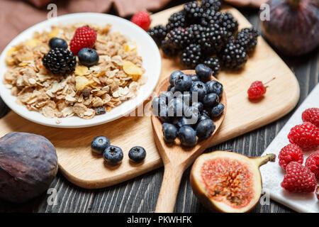 Healthy breakfast set. Muesli and berries on dark rustic background - Stock Photo