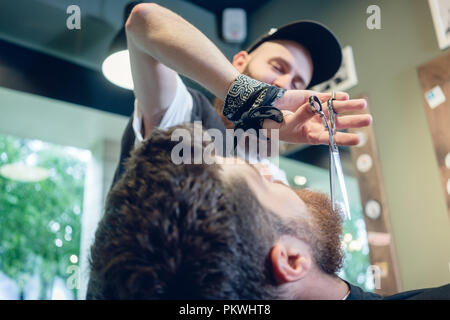 Close-up of the hand of a barber using scissors while trimming - Stock Photo