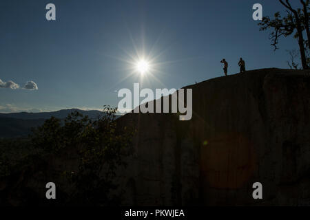 Silhouette of two men on a mountain peak with a sunburst above. Pai Canyon Thailand - Stock Photo