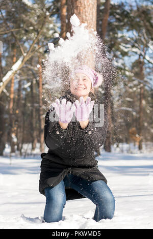 Girl throws snow up. Portrait of the beautiful girl throwing snow in the winter. Happy young woman plays with a snow in sunny winter day. vertical pho - Stock Photo