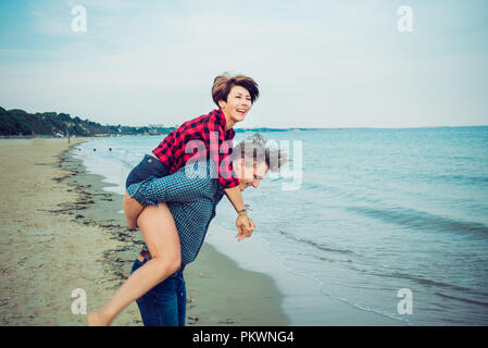 Young men giving piggyback ride to women on beach. Young couple having fun together with blue ocean background. Concept of lovers happy moments on hol - Stock Photo
