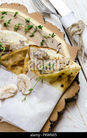 Pancakes with mushrooms and thyme on wooden background. - Stock Photo
