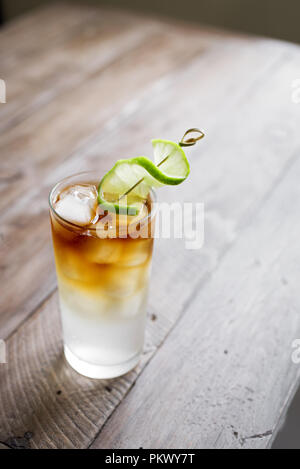 Dark and Stormy Rum Cocktail with Ginger Beer and Lime garnish. Glass of Dark and Stormy Cocktail drink on wooden table, copy space. - Stock Photo