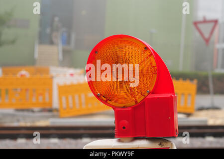 close-up of yellow warning lamp at construction site at misty morning - Stock Photo