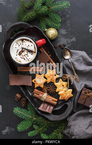 Christmas background with hot chocolate in a red mug with marshmallows, biscuits, spices and chocolate on a dark background. Top view,flat lay - Stock Photo