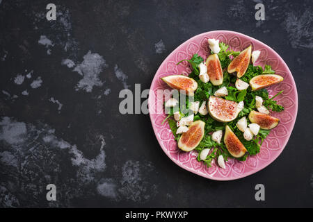 Fresh figs with cheese and greens on a dark concrete background. Flat lay of the copy space. - Stock Photo