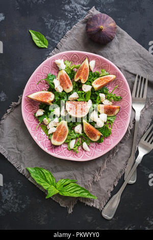 A delicious appetizer of fresh figs,cheese, leaves green. Dark concrete background, flat lay. - Stock Photo