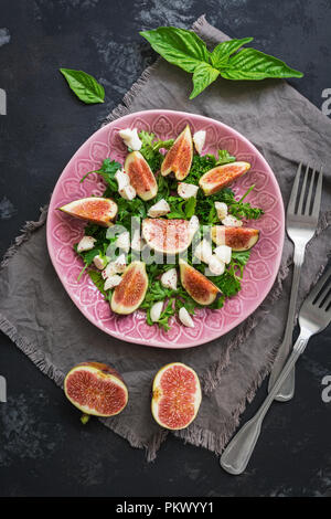 Figs, cheese and fresh greens served on a plate, rustic dark background. Top view,flat lay. - Stock Photo