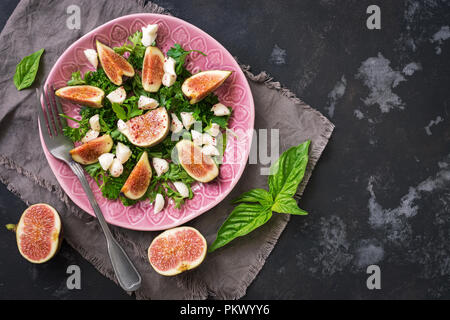 Dietary salad figs, goat cheese, green leaves, dark rustic concrete ofn. Flat lay of the copy space. Mediterranean food. - Stock Photo