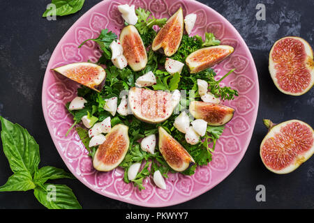 Salad with figs, cheese and greens on a dark concrete background. Dietary healthy food. The view from above, flat lay. - Stock Photo