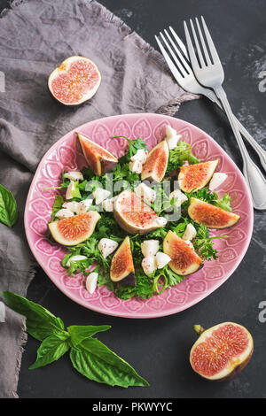 Fresh figs, cheese and greens. Healthy vegetarian salad on a concrete background.Overhead, top view, flat lay - Stock Photo