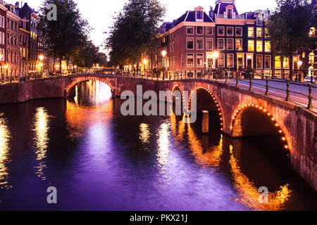 Beautiful night scene from the City of Amsterdam in the Netherlands with canals and lights - Stock Photo