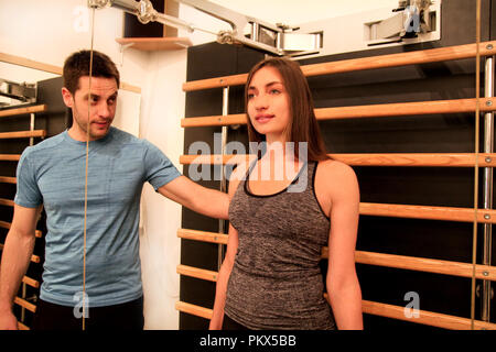 Young woman exercise in a gym with the help of her personal fitness trainer on kinesis technology machine straps in the fitness studio. Sport, fitness - Stock Photo