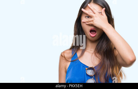 Young asian woman over isolated background peeking in shock covering face and eyes with hand, looking through fingers with embarrassed expression. - Stock Photo