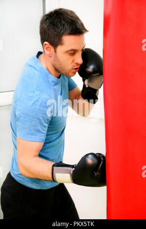 Male boxer training is exercising with a punching bag at the gym club. Portrait of a young athlete handsome sports man in boxing red gloves practicing - Stock Photo