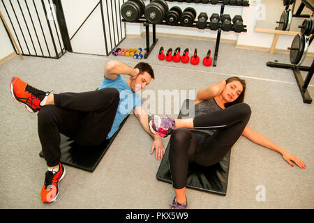 Sporty people doing stomach abs exercises at gym club. Happy fit young pretty couple in training working out stomach on mat in fitness studio. - Stock Photo