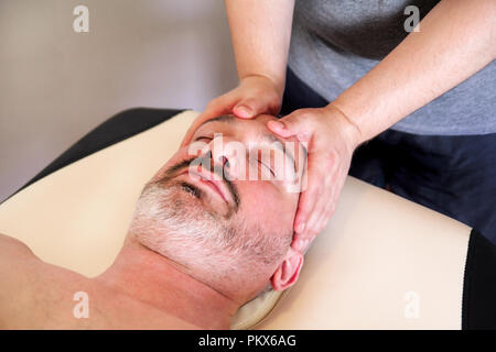 Man having treatment for his face at massage table, medicine concept. Masseur massaging mans face. Handsome man relaxing receiving facial massage. - Stock Photo