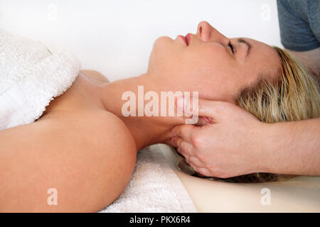 Beautiful woman during and enjoying, receiving a wellness neck massage in spa center, she is very relaxed. Woman receiving neck massage in medical. - Stock Photo