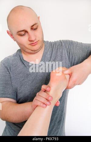 Foot massage in beauty salon, close up view. Woman having sports foot massage in spa salon. Male masseur therapist hands doing on female foot massage. - Stock Photo
