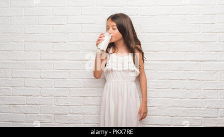 Young hispanic kid over white brick wall drinking a glass of milk with a confident expression on smart face thinking serious - Stock Photo