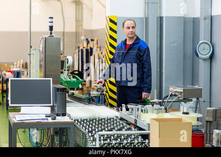 Factory worker controlling a machine working on a production line - Stock Photo
