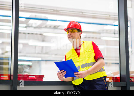 Factory supervisor in yellow reflective west with red helmet. Factory engineer holding blue folder with documents - Stock Photo
