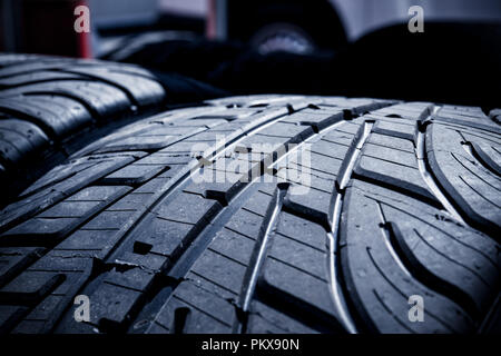 Extreme macro close up of tread grooves on racing car wet tires new set - Stock Photo