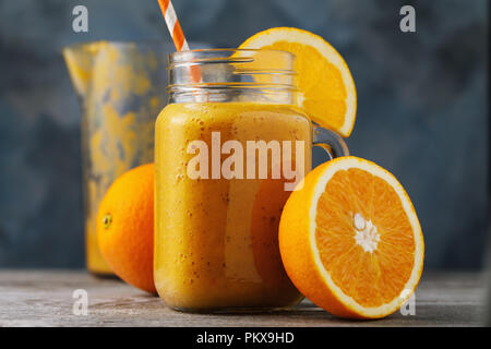 Vitamin drink: smoothies from fresh oranges in a glass jar on a wooden table, close-up - Stock Photo