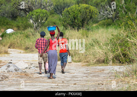 African Woman Walking Carrying Basin on Head and Two Young Men Walking, Africa Woman Carries Load on top of her Head, Uganda - Stock Photo