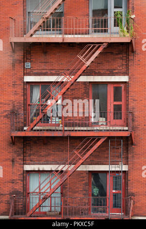 Close-up view of New York City style apartment buildings with emergency stairs along Mott Street in the Chinatown neighborhood of Manhattan NYC. - Stock Photo