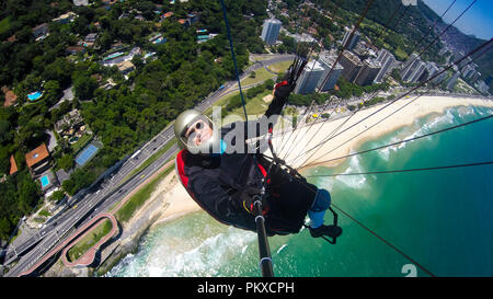 Paraglider pilot, physical handicapped, riding their own paragliding, pure adventure in Rio de Janeiro Brazil - Stock Photo