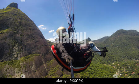 Paraglider pilot, physical handicapped, flying in their own paragliding. - Stock Photo