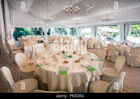 Wedding reception venue in a large marquis with elegant formal white table settings and a view of a garden - Stock Photo