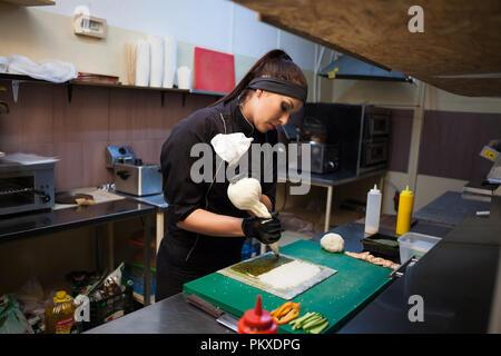 woman Cook prepares sushi on restaurant kitchen - Stock Photo