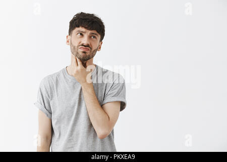 Man having soar throat feeling discomfort and displeasure after eating cold ice cream touching neck and looking at upper right corner with disappointment, frowning suffering from pain - Stock Photo