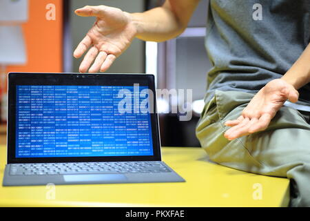 computer coding presentation on screen. mock up blue binary display on laptop monitor. notebook computer on table and hands pointing toward in an invi - Stock Photo